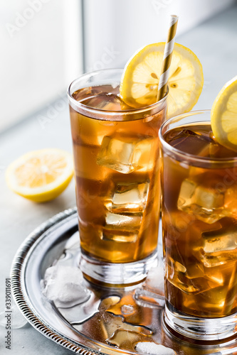 Very close up view of glasses of ice tea and lemon slices on a metal tray against a window sill.