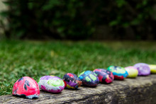 Rocks Painted By A Child With Bright Colors; Painted Rocks Arranged In A Row