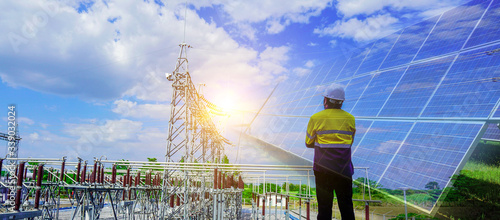 Obraz na plátne Engineer in yellow uniform, and holding a white hat, standing to look at The sunlight that makes solar cells produce clean energy