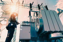 Businessman Wearing A Black Suit, Standing Looking At A Large Power Transformer With Orange Sunlight And White Sky To Be Background, Concept About Business People Who Want To Invest In Energy