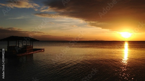 Foto Scenic View Of Boathouse Floating On Sea During Sunset