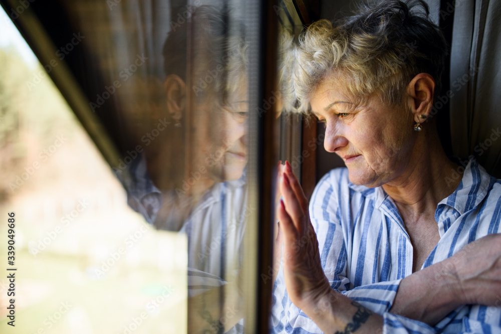 Fototapeta Sad senior woman standing indoors at home, corona virus and quarantine concept.