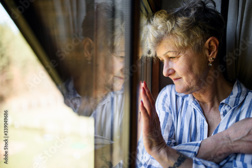 Obraz Sad senior woman standing indoors at home, corona virus and quarantine concept. - fototapety do salonu