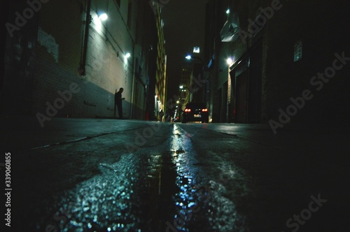 Surface Level Of Alley Amidst Buildings At Night Wallpaper Mural