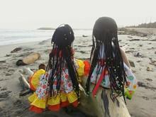 Dolls On Fallen Tree At Beach
