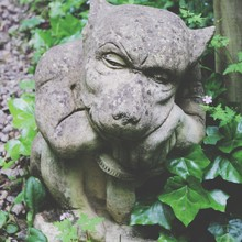 Close-up Of Grotesque Gargoyle In Formal Garden