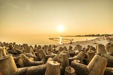 Large Group Of Rocks On Beach Against Sunset Sky