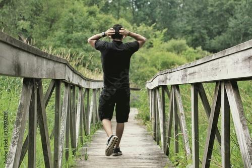 Obraz Rear View Of Man Walking On Footbridge - fototapety do salonu