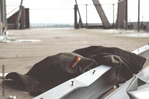 Fotografie, Obraz Abandoned Jacket Beside Girders In Courtyard
