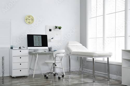 Fotografiet Modern medical office interior with computer and examination table
