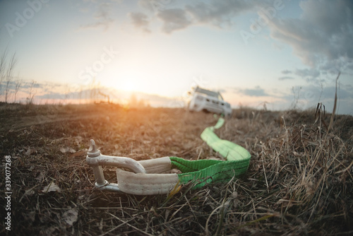 Tow rope with hook and blurred SUV car stuck in a swamp close up. Fototapet
