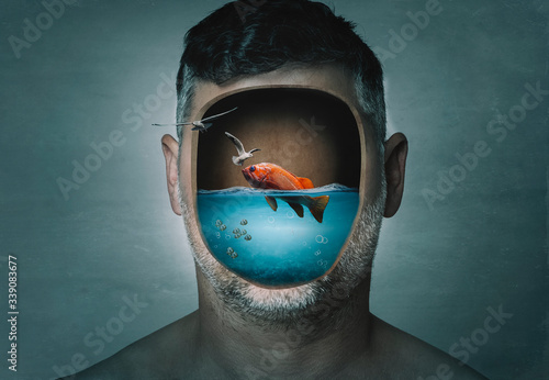 Surreal portrait of man with cropped face filled with water with a fish inside on a blue background Slika na platnu