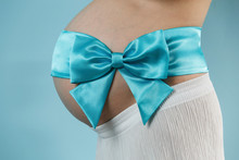 Naked Belly Of Pregnant Woman Tied With A Blue Ribbon Bow With Copy Space For Text . Portrait Of Health Pregnant Woman On  Blue Background Close Up. 9 Month Of Healthy Pregnancy And Motherhood.
