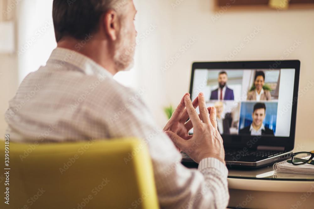 Fototapeta Man working from home having online group videoconference on laptop