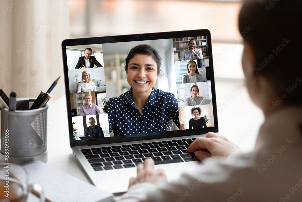 Fototapeta Woman sit at desk looking at computer screen where collage of diverse people webcam view. Indian ethnicity young woman lead video call distant chat, group of different mates using videoconference app