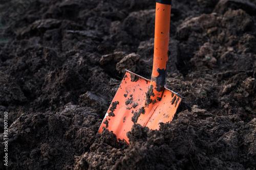 Spade in ground in garden. Orange shovel Fototapet