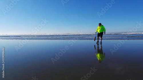 Fotografie, Tablou Man Clamming On Wet Shore Against Sky