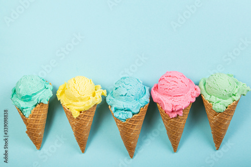 Fototapeta Pastel ice cream in waffle cones, bright background, copy space