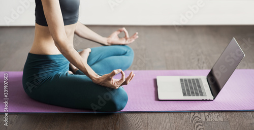Leinwand Poster Young woman practicing yoga at home, online video training, Girl doing exercises