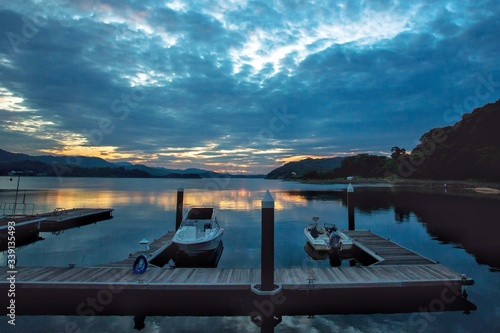 Fotografia Motorboats Moored By Pier In Lake Against Cloudy Sunset Sky