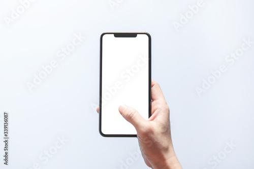 Obraz Smartphone mockup. Close up hand holding black phone white screen. Isolated on white background. Mobile phone frameless design concept. - fototapety do salonu