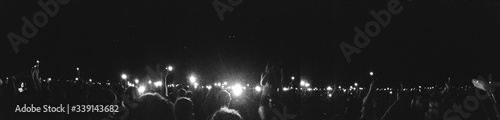 Fotografie, Tablou Panoramic Shot Of Crowd In Music Concert Against Sky At Night