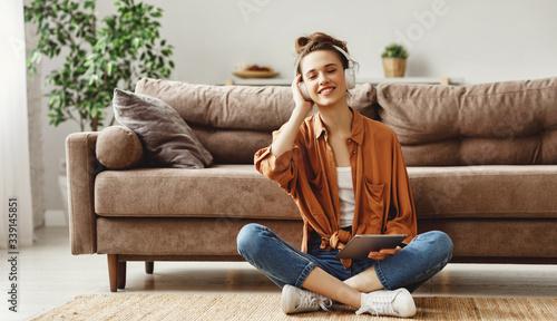 Happy pensive woman using digital tablet at home. Fototapeta