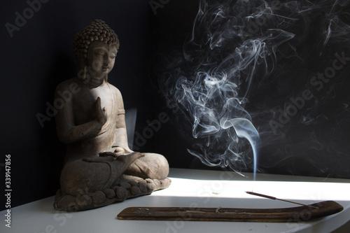 Obraz na plátně Buddha statue with incense stick into sun light on black background mental healt