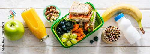 Fotografering Back to school concept - lunch box with juice, apple and banana, copy space