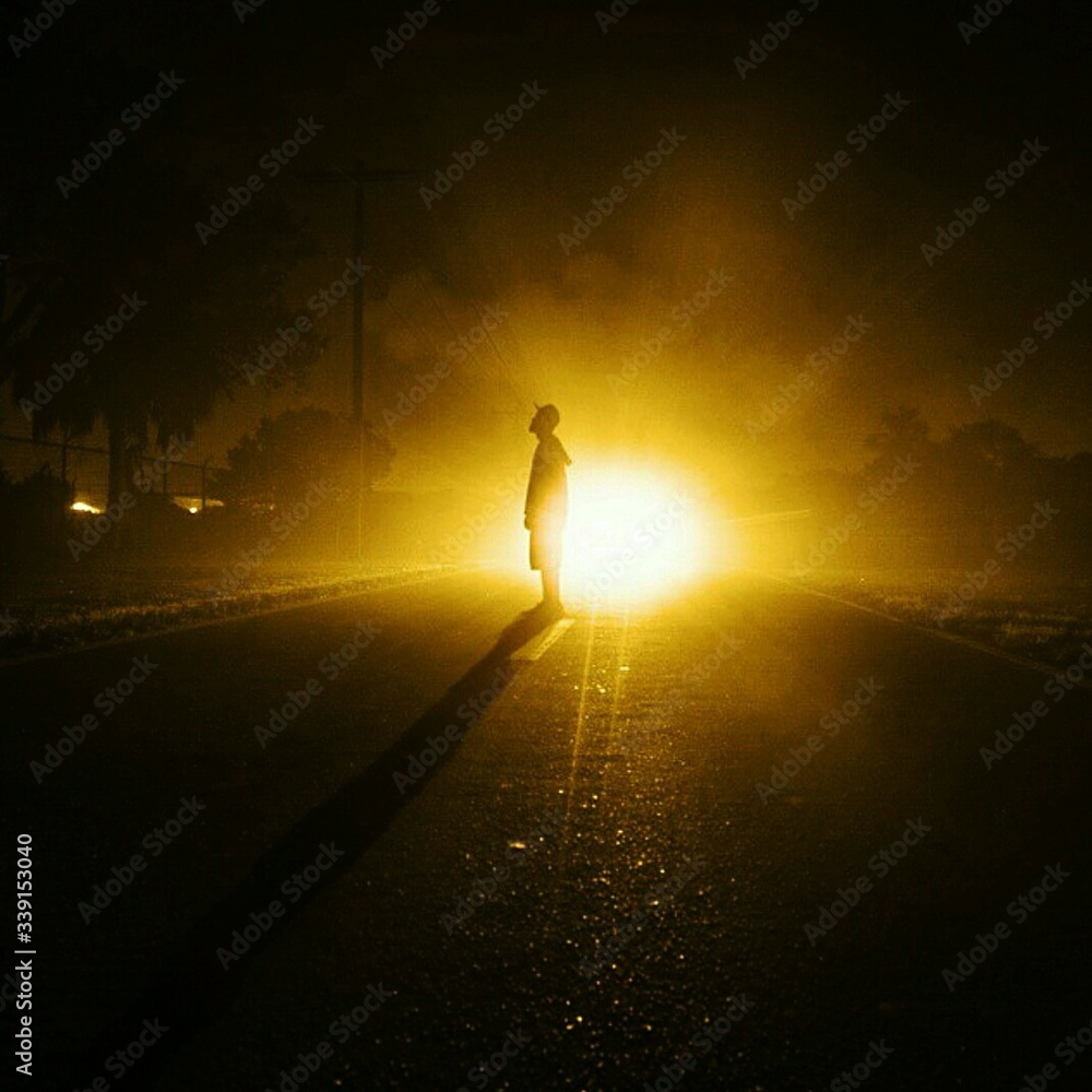 Fototapeta Boy Standing On Street Against Car At Night