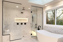 Detailes Of The Larhe Walk In Shower With White Marble And Mosaic, Light. Three Handles, Shower Head In Dark Brass.and Free Standing Modern Tub.