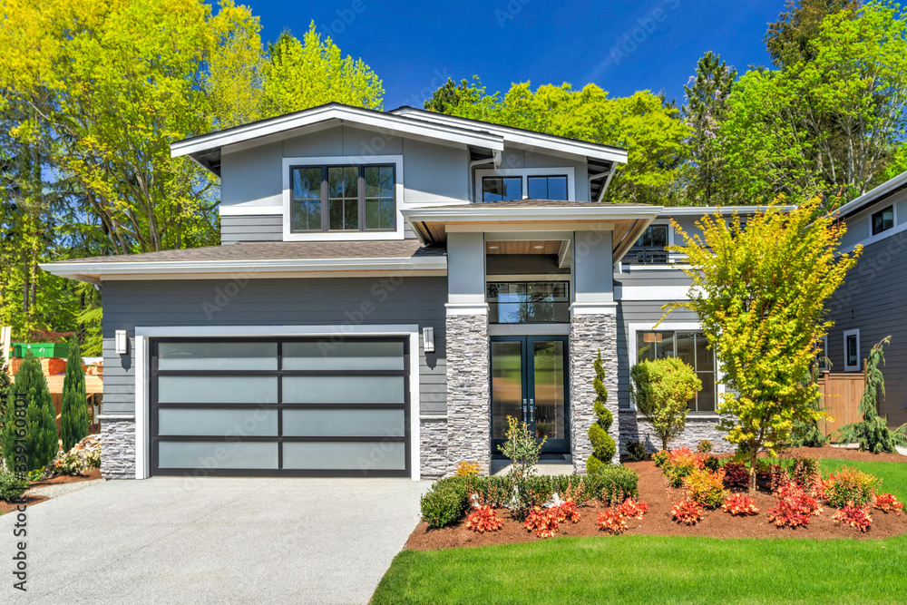 Fototapeta Modern contemporary house exterior with luxury details, landscaping, stone, wood, glass, lots of large windows.