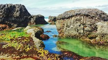 Rocks By Sea Against Sky In Oregon Coast