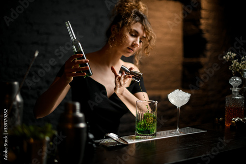 Fotografie, Obraz pretty girl bartender in black blouse carefully pours drink from jigger into mixing cup