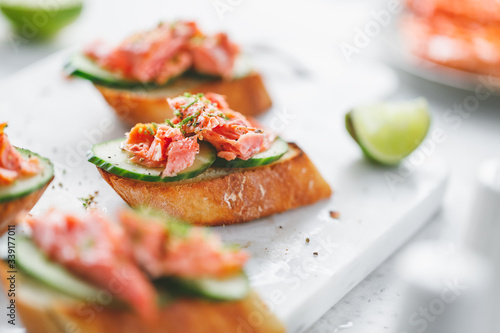 Toasts with fresh cucumber and smoked salmon served with lime shavings Canvas