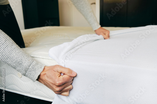 Foto man covering a mattress with a mattress protector