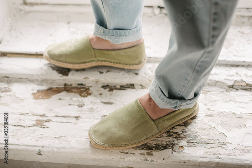 Fototapeta Large foot of a man with light blue jeans and not new green espadrilles against the background of a white painted old window sill, horizontal obraz