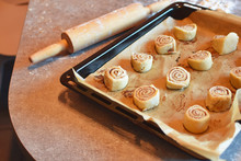 Homemade Unbaked Cinnamon Bans Rolls In Baking Pan On Kitchen Table.