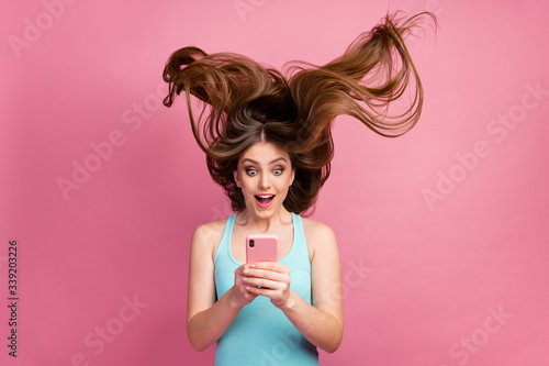 Fototapeta Portrait of her she nice attractive lovely charming cheerful cheery straight-haired girl using digital device 5g app ideal silky soft hair flying isolated on pink pastel color background obraz