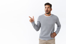 Shocked Slightly Worried Handsome Bearded Caucasian Guy In Grey Trendy Sweater, Gasping Drop Jaw From Amazement, Look Concern, Pointing Left Shook And Speechless, Check Out Something Unusual