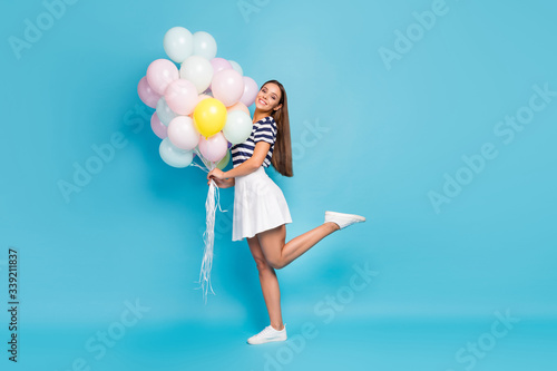 Obraz Full length profile photo of beautiful pretty lady good mood bring many air balloons friend birthday event wear striped t-shirt white short skirt footwear isolated blue color background - fototapety do salonu