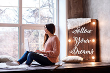 Attractive Young Girl Is Working Or Studying At Home Using Her Laptop. Follow Your Dreams Motivation Lettering Written On The Lightboard.