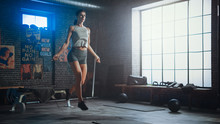 Strong Athletic Woman Exercises With Jumping Rope In A Loft Style Industrial Gym. She's Concentrated On Her Intense Cross Fitness Training Program. Facility Has Motivational Posters On The Wall.