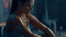 Beautiful Strong Fit Brunette In Sport Top And Shorts In A Loft Industrial Gym With Motivational Posters. She's Catching Her Breath After Intense Fitness Training Workout. Sweat All Over Her Face.