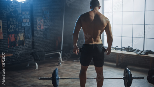 Fotografie, Obraz Handsome Muscular Man Does Overhead Deadlift with a Barbell in a Small Authentic Gym