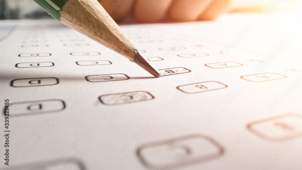 Fototapeta On Exam Test Person Colors Right Answers with a Pencil. Filling up Answer Sheet with Standardized Tests, Marking Correct Answer Bubbles