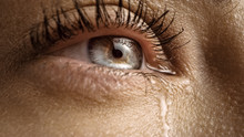 Close Up Macro Shot Of A Crying Eye. Young Beatiful Female With Natural Light Blue, Yellow And Brown Color Pigmentation On The Iris. Mascara Is Applied To Eyelashes. Tears Are Flowing Down.