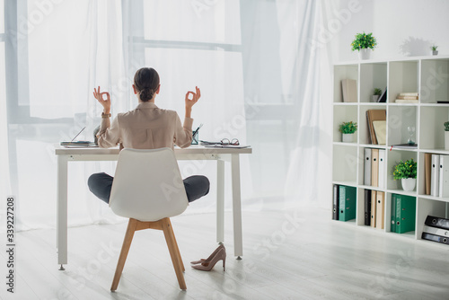 Obraz Back view of businesswoman meditating in lotus pose with gyan mudra at workplace - fototapety do salonu