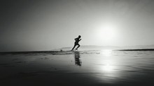 Silhouette Man Running In Water At Beach