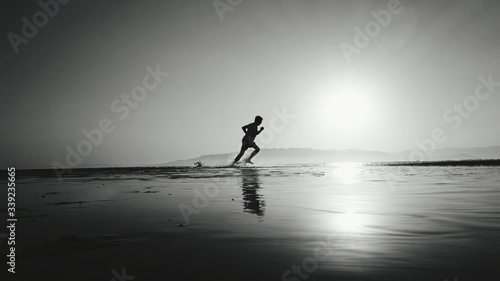 Obraz Silhouette Man Running In Water At Beach - fototapety do salonu